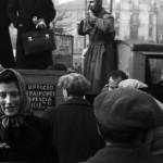 Persone in attesa di salire su un camion con la scritta: Ufficio Trasporti Brescia, Milano 1945-46.